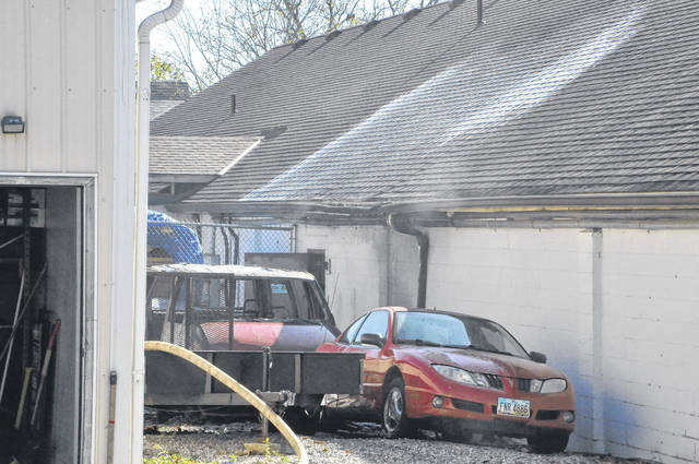 A burned vehicle sits between the buildings at 77 Noble Street. Fire officials said they were initially called to the scene to investigate the vehicle fire and then battled the fire on the two nearby roofs. They could not say definitively Tuesday morning if the vehicle fire caused the fire on the two buildings.