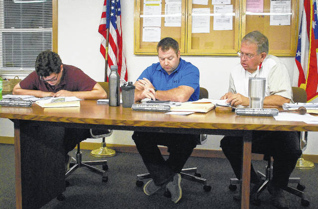 Berlin Township trustees, from left, Adam Fleisher, Steve Flaherty, and Ron Bullard look over a letter of opposition that was hand delievered to them by a resident Monday evening during the rezoning hearing.