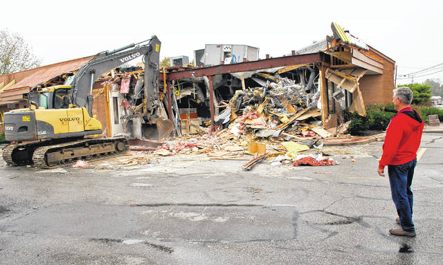 Demolition of the McDonald's on U.S. 23 north of Delaware began Wednesday morning to make room for an upgraded store that will be completed at the end of December. Rod Boester watches as the backhoe grabs the edge of the 1985 building and pulls it to the ground.