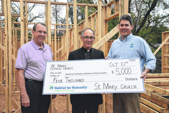 Larry Hanna and Father Michael Watson of St. Mary Church present their Apostles Build V donation to Todd Miller, Executive Director of Habitat for Humanity of Delaware & Union Counties.