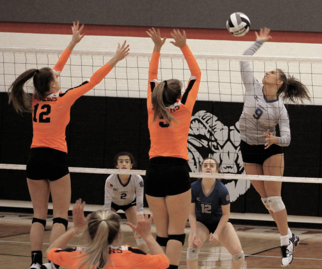 Liberty's Heather Littlejohn (9) winds up for a kill while Hayes' Ally James (5) and Hadlee Bruns (12) attempt to block it during the first set of Thursday's Division I district semifinal in Whitehall.