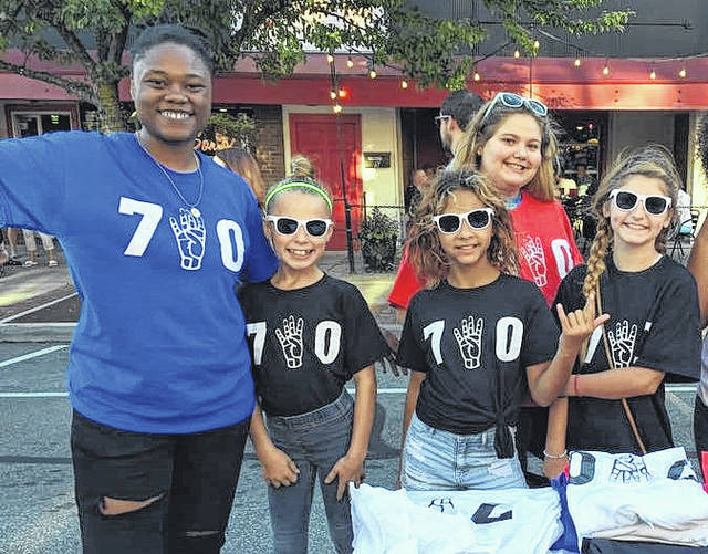 "Braje Brewer, far left, Delaware resident and owner of 7FortyGear, poses for a photograph with several customers sporting her ""740"" T-shirts during a First Friday event held in downtown Delaware in August. Currently, Brewer is selling her T-shirts via the 7FortyGear Facebook page. In 2018, she plans to unveil her own website along with a new line of colors."