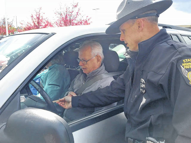 Trooper Ron Scheider from Granville ensures Delaware resident Frank Roell is proper distance from the steering wheel. Roell's wife, Lou Ann Roell is seated in the passenger seat.