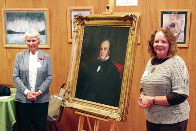 Donna Meyer, right, executive director of the Delaware County Historical Society, accepts the donation of a portrait of Judge Hosea Williams from Louise Warner, founder and board member of the Stratford Ecological Center. Warner is a descendant of Williams. The portrait will hang in the Historical Society's Meeker Homestead Museum.