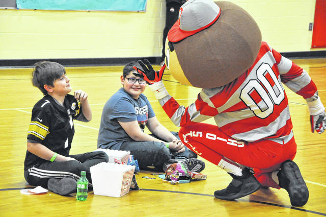 Brutus the Buckeye teases a Conger Elementary School student for wearing Pittsburgh Steelers merchandise on Wednesday afternoon at Conger. Brutus visited students who excelled at the Read-A-Thon and posed for photos and goofed around with the students.