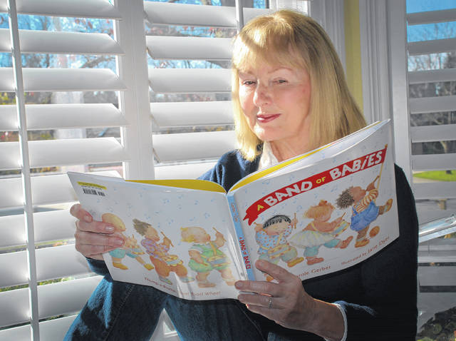 "Award-winning author Carole Gerber sits in her dining room bay window leafing through the pages of her book ""A Band of Babies."" The book was announced as one of Amazon's <a href=""https://www.amazon.com/b/ref=s9_acss_bw_cg_BOTYkid_2a1_w?node=17296347011&pf_rd_m=ATVPDKIKX0DER&pf_rd_s=merchandised-search-3&pf_rd_r=XYDGR59HRAVWNJ57W2GS&pf_rd_t=101&pf_rd_p=08d8d9a7-6964-4761-b65c-474e8a731267&pf_rd_i=17296227011"">""20 Best Children's Books of 2017</a>"" last week."