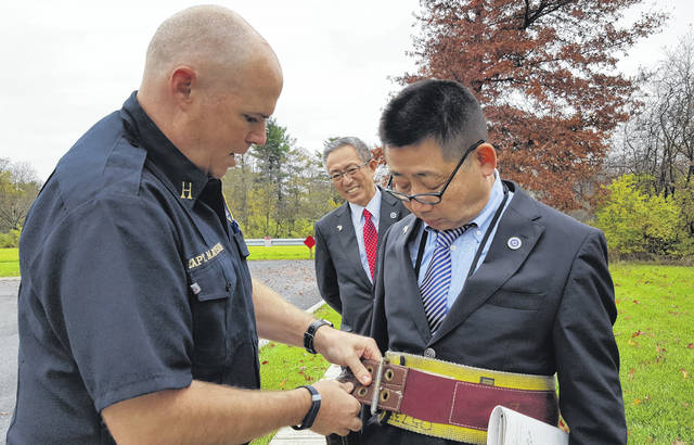 Delaware Fire Capt. Alan Matteson helps Hideo Kishiya, director of the Sakata (Japan) City Library, with his safety belt while Hitoshi Nagata, director general of the City of Sakata Policy Promotion Department, looks on in the background.