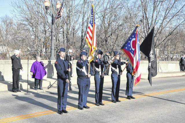 Members of the Delaware Hayes High School R.O.T.C. Honor Guard present the Colors on Sunday afternoon while Mary Bloch sings The National Anthem during the Pearl Harbor remembrance ceremony. The event was held on the Winter Street bridge in Delaware.