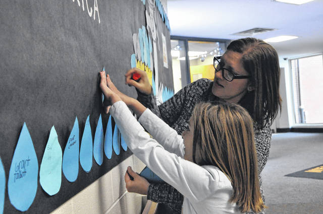 Carlisle Elementary School Library Media Specialist Carrie Abahazi hangs up water drops with third-grader Ava Anthony Friday morning. Students and staff at the school have raised nearly $500 that will be donated to build a well in a community in Africa.