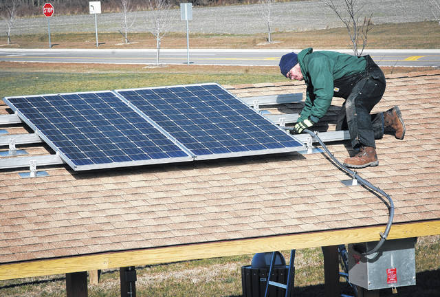 Mike Kelly, a facilities and equipment worker, inspects the solar panel on top of the Orange Bridge Park shelter house. The panel was installed just before the park opened Oct. 9, 2016. Beth Hugh, Orange Township parks director, said the panel and transformer will only power a couple of crockpots and a boombox.