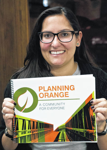 Orange Township's Planning and Zoning Director Michele Boni displays the township's new Comprehensive Land Use Plan. The township partnered with graduate students from The Ohio State University, who conducted surveys and compiled the data to create the plan.