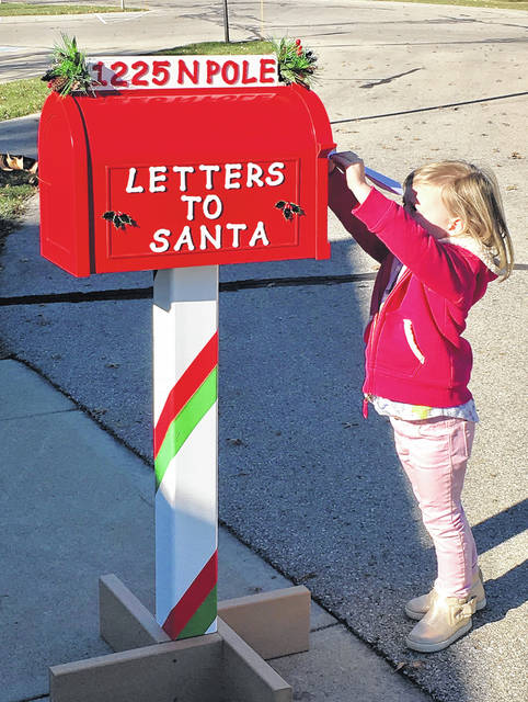Santa Claus has placed one of his special mailboxes in front of Orange Township Hall for children to mail letters to him. Santa said he would respond to all letters received by Dec. 17 that have both the child's name and address on the envelope. Taking advantage of the mailbox by getting her letter in early is Hattie Alt.