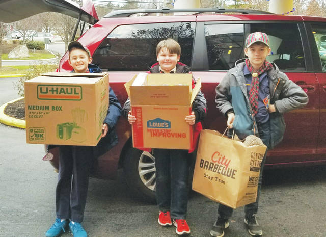 Boy Scouts Matt Barker, Andrew Carr, and Luke Kinder are ready to drop off armloads of Christmas presents during the annual Gifts for Grady program. Local Scouts have been donating toys to OhioHealth Grady Memorial Hospital for 11 years.