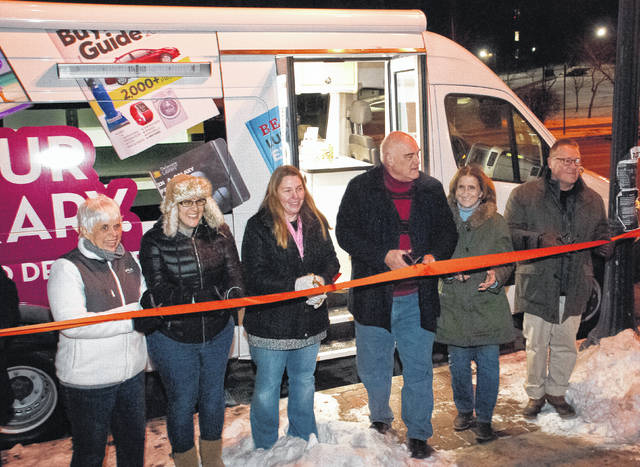 Though the shelves are currently empty of books and other library materials — that's just how new it is — the Delaware County District Library's new bookmobile received a grand ribbon-cutting ceremony by members of the library board, employees, and Friends of the Library during Main Street Delaware's January First Friday. After the ribbon cutting, the vehicle was opened to the public to take a look inside. Robbie Apt, outreach manager, said the bookmobile is an extension of the library branches that reaches hundreds of individuals each week. Pictured cutting the ribbon are, from left to right, Karen Cowan, Friends of the Library president; Deputy Director Molly Labadie; Robbie Apt; DCDL Director George Needham; Holly Quaine, member of the library board and president of the Delaware Area Chamber of Commerce; and Neil Neidhardt, member of the library board.