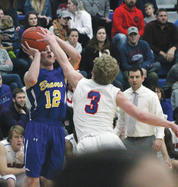 Olentangy's Sean Marks (12) launches a three-pointer over Orange's Luke Ballinger during the first half of Friday's OCC showdown in Lewis Center.