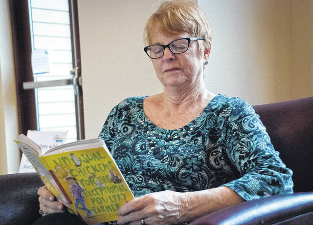 """Pen pal Pat Holobaugh sits in the lobby at SourcePoint catching up on the book """"Unusual Chickens for the Exceptional Poultry Farmer,"""" which Conger Elementary students are reading as part of the pen pal program. Holobaugh said she was a little behind in the book and needed to catch up."""