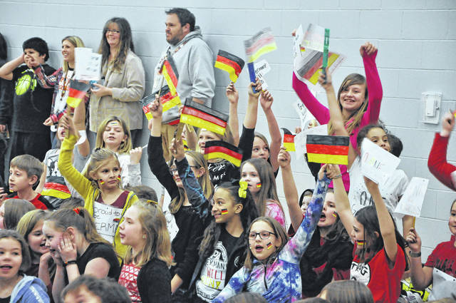 "Smith students from Team Germany cheer during the kick off for the Reading Olympics Friday afternoon. For the next two weeks, students will be asked to keep track of how many minutes they read. The ""country"" with the most minutes gets a special prize"