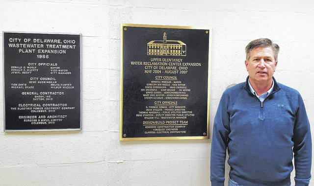 Former City of Delaware Public Utilities Director Brad Stanton, who retired Wednesday, poses for a photo beside two plaques acknowledging two of the most recent expansion projects on the Upper Olentangy Water Reclamation Center at 225 Cherry St