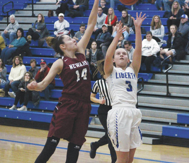 Liberty's Emma Humenay (3) puts up a shot while being defended by Newark's Katie Shumate (14) during the first half of Monday's non-league showdown in Powell.