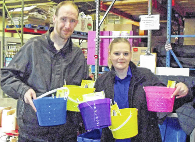 Tia Mann and her husband, Jesse Mann, pose with Easter baskets that were donated during the drive last year.