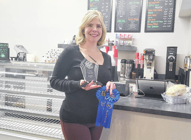 "Delaware resident Jennifer Butler poses inside Fresh Start Café & Bakery in downtown Delaware with her ""Best Baker 2018"" trophy and two first-place ribbons after winning the inaugural Fresh Start Baking Championship."