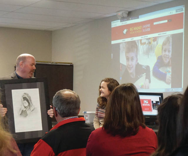Brad Schneider, a member of the Big Walnut Board of Education, congratulates Alexa DeGenova for being named Big Walnut Middle School Art Student of the Month during a board meeting held March 15 in Sunbury.