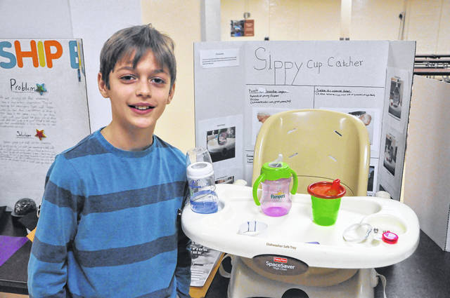 Nicholas Hejmanowski, a fifth-grader at Smith Elementary in Delaware, stands in front of his invention, The Sippy Cup Catcher, Tuesday during the Invention Convention. Hejmanowski devised a contraption consisting of a retractable cord and elastic band to prevent sippy cups from falling to the ground.