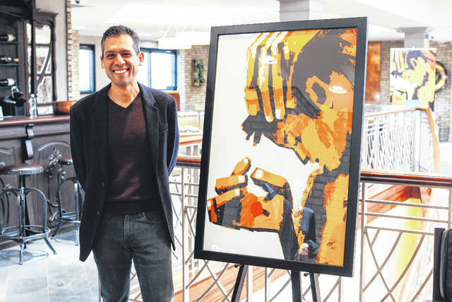 Delaware resident and artist Jeremy Rosario poses in front of one of his pieces about the aftermath of Hurricane Maria. Rosario said all of the pieces on display are about the human reaction to the devastation, and they show isolation, grief and hope.