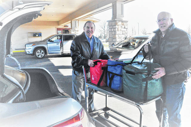 Delaware County Auditor George Kaitsa, left, and Meals on Wheels volunteer Steve Conway, right, load meals into Conway's car for delivery Tuesday.