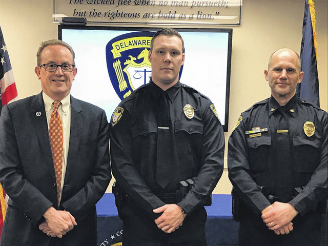Officer Sam Walter, middle, poses with Delaware City Manager R. Thomas Homan, left, and Delaware Police Chief Bruce Pijanowski, right, after he was sworn in on March 22.