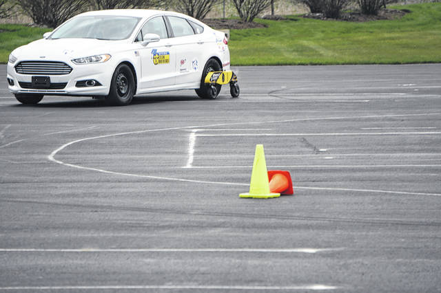 "A ""skid car"" — a Ford Focus equipped with hydraulics to provide less traction for the rear wheels — drives on a course set up in the parking lot of A.D. Farrow in Sunbury on April 17."