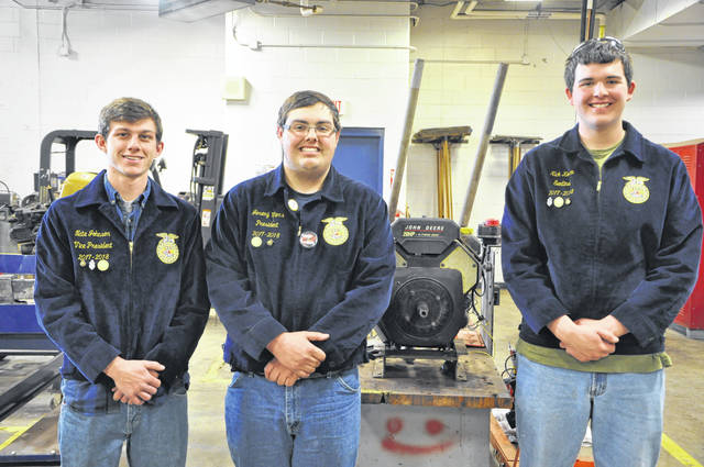 From left to right: Nate Johnson, Jeremy Viers, and Nick Koren pose next to a John Deere engine they've used to practice with in their class in the power sports program at the Delaware Area Career Center.