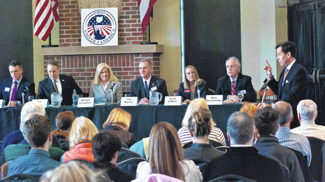 WBNS Columbus news anchor Scott Light, standing to the far right, moderated a GOP candidate debate for the 12th Congressional District primary Saturday at Ohio Wesleyan Unversity's Hamilton-Williams Campus Center. Sitting at the table, left to right, are candidates Jon Halverstadt, Tim Kane, Melanie Leneghan, Pat Manley, Carol O'Brien and Mick Shoemaker. Troy Balderson, not shown, was to the left of Halverstadt.