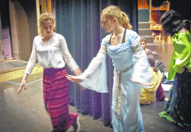 "Backstage on Thursday evening at Buckeye Valley High School, students Alexa Draper, left, and Clare Digrandi, right, practice their dance steps before going on stage to rehearse for ""Once Upon a Mattress."" In a last minute shakedown of the new lighting system, Peter Naumenko, a lighting specialist with Demmer Solutions Audio and Video of Columbus, shows Robin Wilson, a Buckeye Valley High School student, how to use the new touchscreen system. ""Once Upon a Mattress"" will be the first production to use the system."