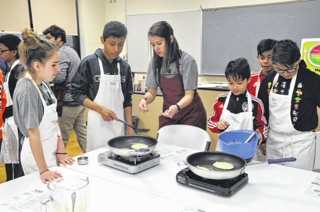 Ohio Wesleyan University senior Hallie Sinko (center in gray) teaches students how to make orange oatmeal pancakes in the Cooking Matters course during the United Way's Strengthening Families Spring Break activities at Willis Education Center.