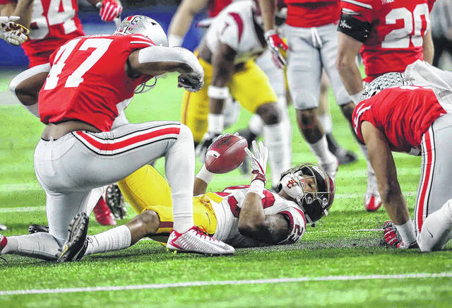 Ohio State linebacker Justin Hilliard (47) celebrates with teammate Austin Mack after they made a tackle on a kickoff return by USC's Velus Jones (23) in the Cotton Bowl.