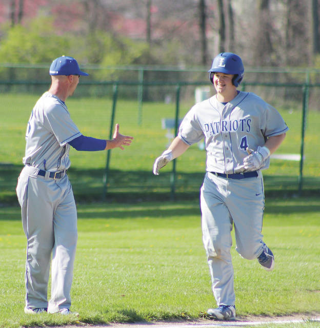 Liberty's Justin Nelson is congratulated by head coach Ty Brenning after connecting on a two-run homer in the second inning of Monday's OCC showdown against host Westerville North.