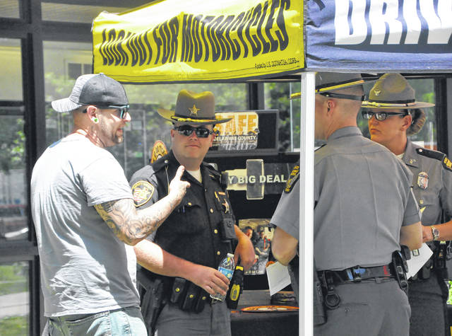 A motorist who stopped at the southbound rest area on Interstate 71 on Friday afternoon speaks to a deputy from the Delaware County Sheriff's Office and two troopers from the Ohio State Highway patrol during an outreach effort put on by several agencies in hopes of keeping the roadways safe over the Memorial Day weekend.