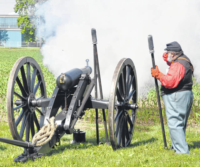 Rick Helwig covers his ear after Henry Shaw Jr., not pictured, fired a replica of a Civil War-era cannon known as a 6-pounder Wiard rifle. Both men are part of the 5th Ohio Light Artillery Unit.