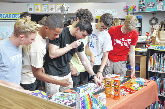 Hayes seniors look at old yearbooks Monday during the Senior Recognition Luncheon at Smith Elementary School. School officials asked the visiting seniors to sign their names on the frames around the old class photos, so the frames could be displayed in the school.