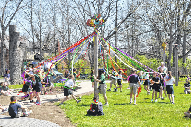 Fourth- and fifth-graders from St. Mary School perform a dance around the maypole Tuesday at Boardman Arts Park in Delaware. The poles, used to hold volleyball nets, were decorated by Creative Foundations for the celebration. St. Mary music teacher John Blakeslee (on right side in blue) said he spent three or four weeks teaching the dance to the students.