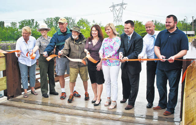 Coming from out under their umbrellas long enough to participate in a ribbon-cutting ceremony, officials from Orange Township's Park Department, the U.S. Army Corps of Engineers, and the Ohio Department of Natural Resources officially opened the new bike/pedestrian bridge that spans the spillway of the Alum Creek Dam. The bridge now offers a safer connection from the trails of Alum Creek to the Orange Township Trail System.