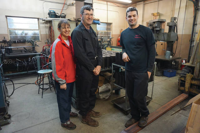 The Harp family — Beth, Rodney and Kurtis — stand by a machine in their Sunbury shop.