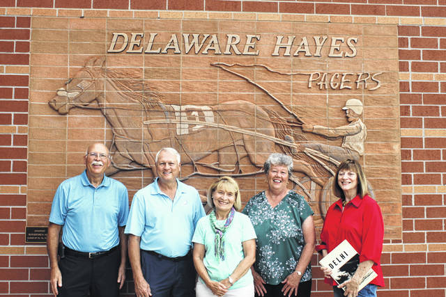 From left to right: Fred Blakeslee, Bob Schultz, Patricia Stout, Debi Hoskins Bauder and Alex Reed Fogle pose for a photo on the west side of Hayes High School Thursday. The group will celebrate its 50th year class reunion in August during a series of events.