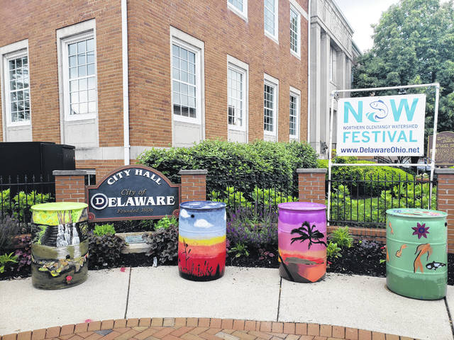 Rain barrels and a sign promoting the upcoming fifth annual Northern Olentangy Watershed (NOW) Festival are on display outside Delaware City Hall at the corner of South Sandusky and East William streets. The city reports the majority of rain barrels were painted by local school districts throughout the upper Olentangy Watershed, and the barrels will be raffled off at the event with the proceeds going to improve the Olentangy Watershed.