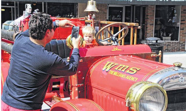 Grant Baker, 2, sits behind the wheel of a vintage Delaware Fire Department truck during a previous Performance Classic Car Show. Grant's dad, Josh Baker, snaps a photo of his little firefighter. Josh said it took a little while for Grant to get warmed up, but he was having a good time checking out all of the vehicles.