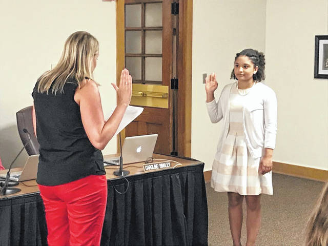 Student board member Caroline Binkley is sworn in by DCS Treasurer Melissa Lee at the board meeting on June 18.