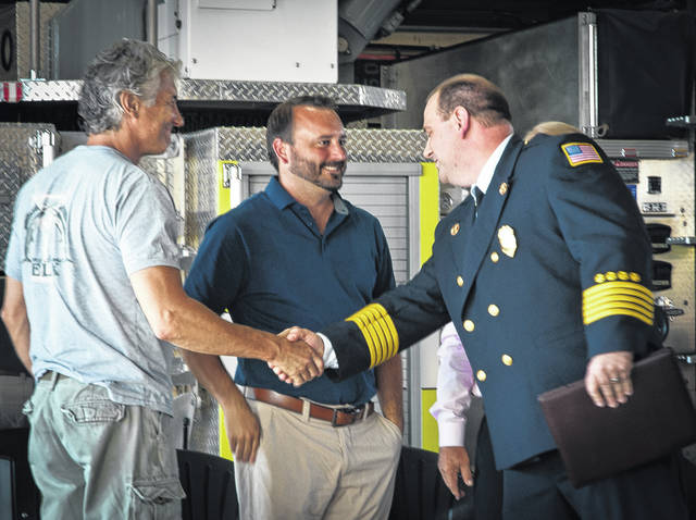 After being sworn in and having his badge pinned to his chest, Fire Chief Christopher Kovach shakes hands with the board members of the Berkshire, Sunbury, Trenton and Galena Fire District. After an 18-month search, Kovach was chosen from several applicants to serve as the district's new fire chief.