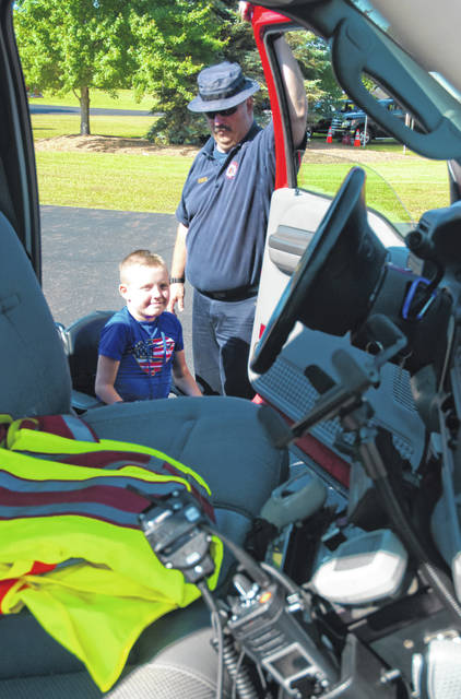 Recreation Unlimited camper Tristen Waller, left, of Beverly, marveled at the equipment in one of Tri-Township's utility vehicles as Troy Morris, right, a Tri-Township firefighter, explains what each piece of gear does and how it is beneficial in fighting fires and performing rescues.