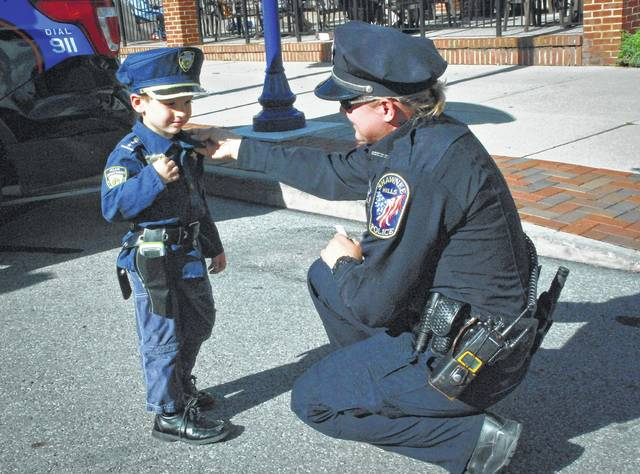 In this Delaware Gazette file photo, Shawnee Hills Police Officer LC Goetz double checks Tanner Kongo's attire to make sure all is according to uniform codes before Delaware's First Friday Picnic with a Cop event last year. Kongo looked at every piece of police equipment and shook the hand of every police officer at the Friday evening event. Kongo said when he grows up, he wants to be the chief of police just like his friend Delaware City Police Chief Bruce Pijanowski.